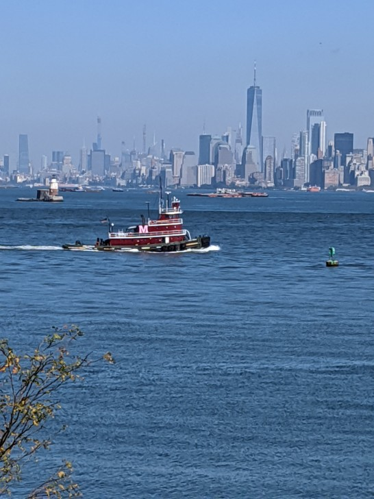 view of Manhattan skyline from Empire Outlets in Staten Island, with red tugboat, photo by LensMomentsNS - Nichole Spates 2019
