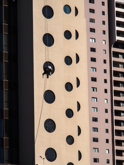 a photo of a window washer at work in waikiki, honolulu a photo by LensMomentsNS - Nichole Spates 2018