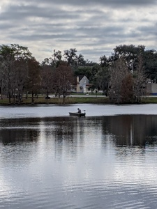 A photo of a man in a small boat on a small lake on a gray day by LensMomentsNS - Nichole Spates 2021
